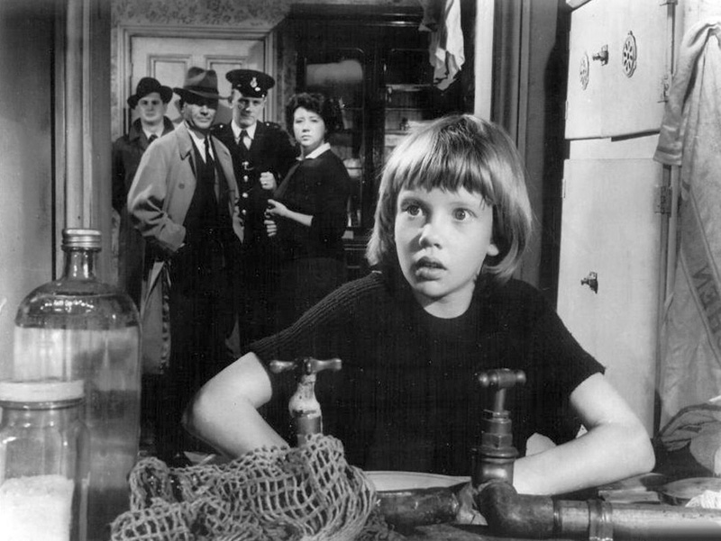 "Hayley Mills with father John Mills in the background as police inspector in ""Tiger Bay"""