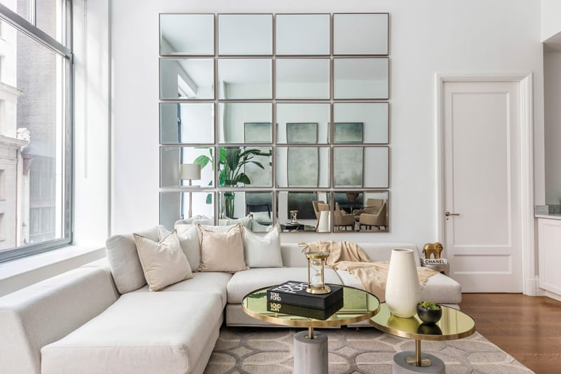 Identical rectangular mirrors hung in a grid pattern help add height to a loft-like living space | Photograph courtesy of Design Recipes