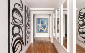 A series of mirrors placed across from artwork helps elongate a hallway. (Scott Morris/Design Recipes) Image