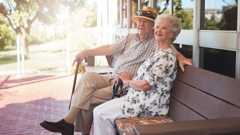 Retired couple sitting on a bench outside their home Image