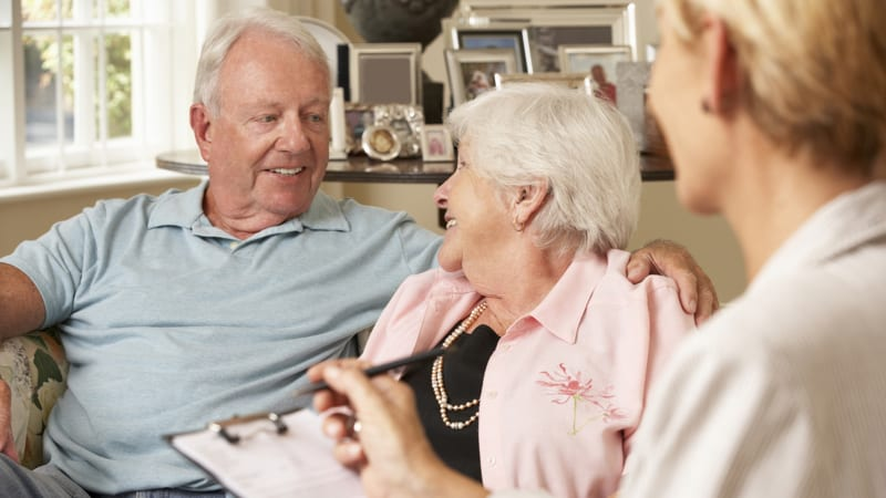 Retired Senior Couple Sitting On Sofa Talking To Financial Advisor Image