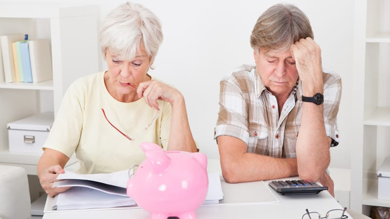Portrait Of Upset Senior Couple Calculating Finance At Home Image
