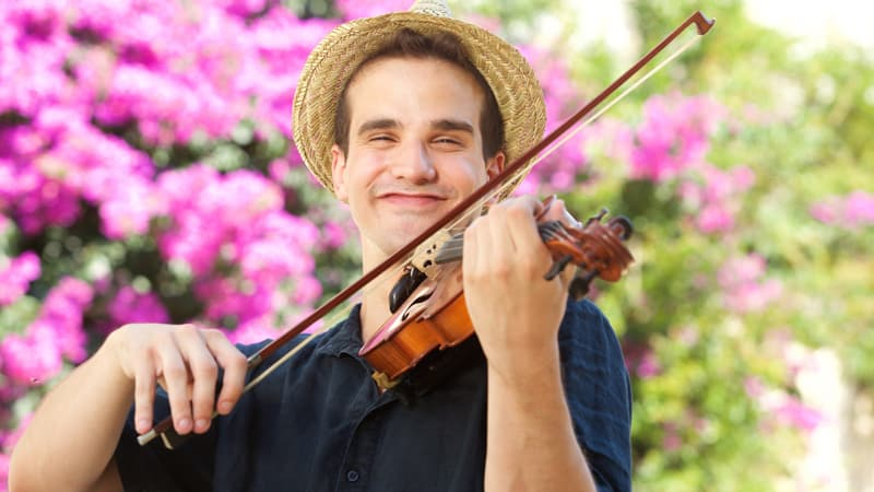 Happy man playing violin outside Image