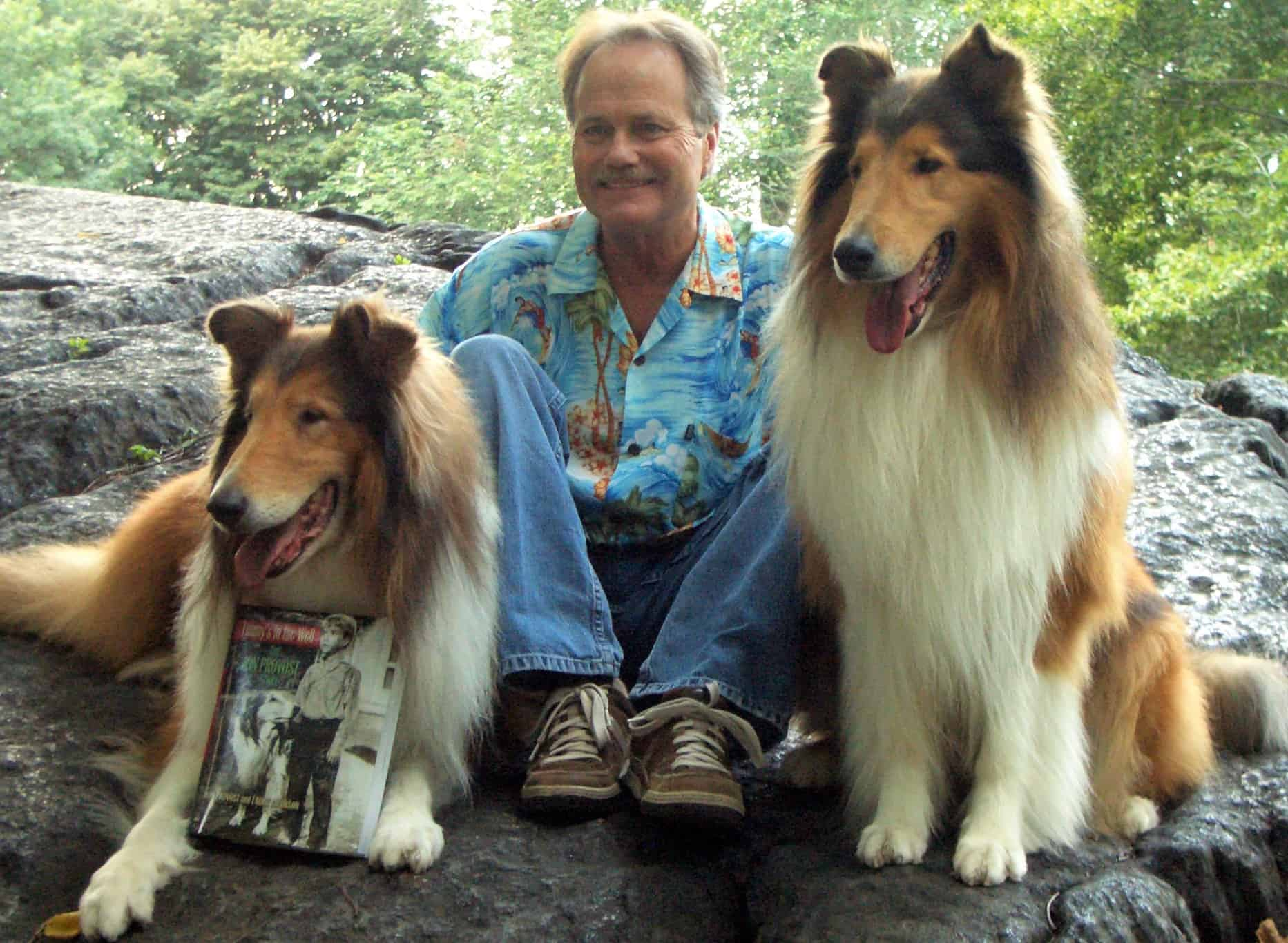 Jon Provost displays a copy of his autobiography with the help of a couple of four-legged friends