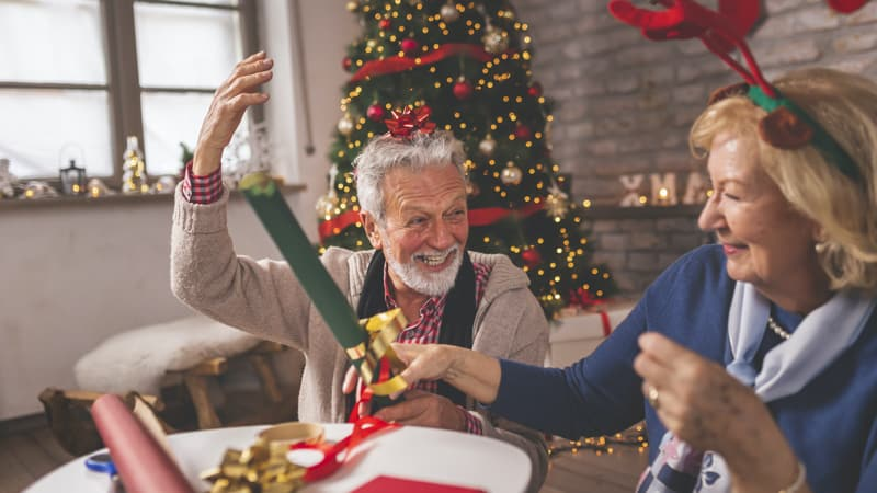 Senior couple wrapping Christmas presents to keep holiday cheer high and avoid getting stressed out Image