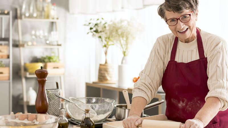 Senior woman cooking after following our tips for clearing up a holiday kitchen Image