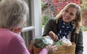 A woman volunteering with Naborforce brings an elderly local groceries Image