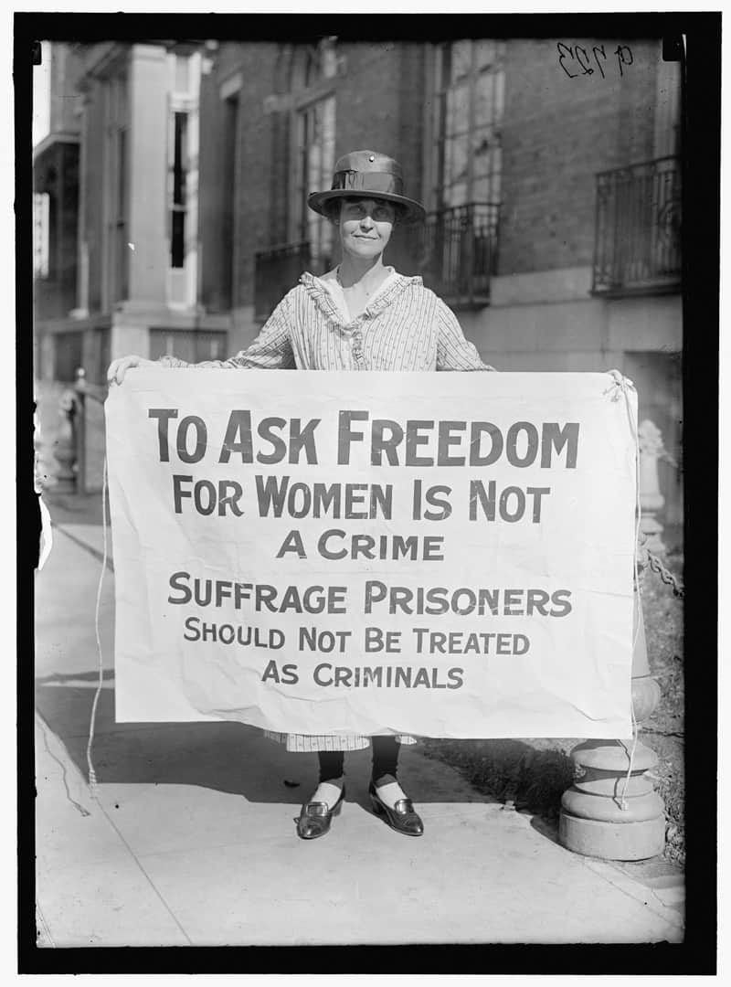 Suffragette holding a sign promoting women's right to vote