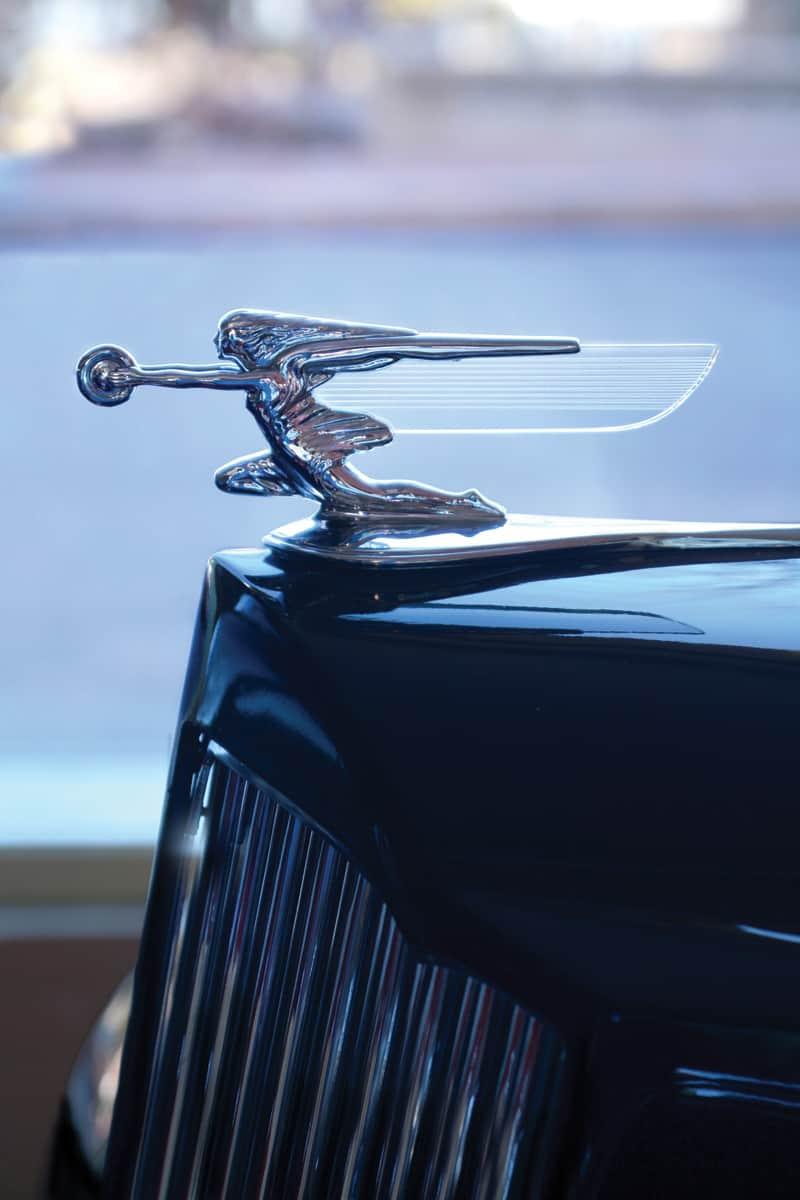 A sculptural '38 Packard Goddess of Speed radiator mascot atop a Packard One-Twenty Convertible Coupe