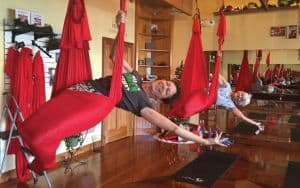 Two women perform aerial yoga at Fighting Gravity Fitness Image