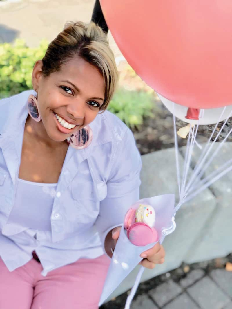 Kisha Frazier, owner of Hummingbirds Macarons & Desserts, holds a balloon