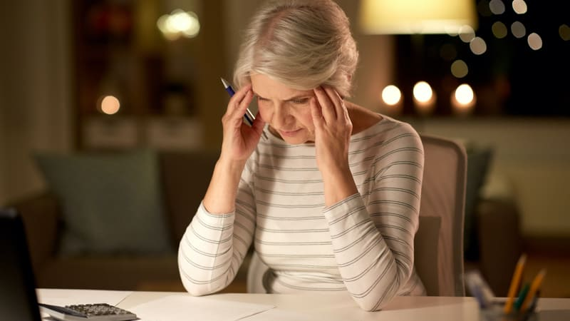 Stressed senior woman staring at service club papers and getting stressed Image