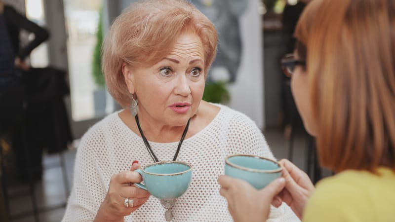 Two mature women drinking tea and gossiping Image