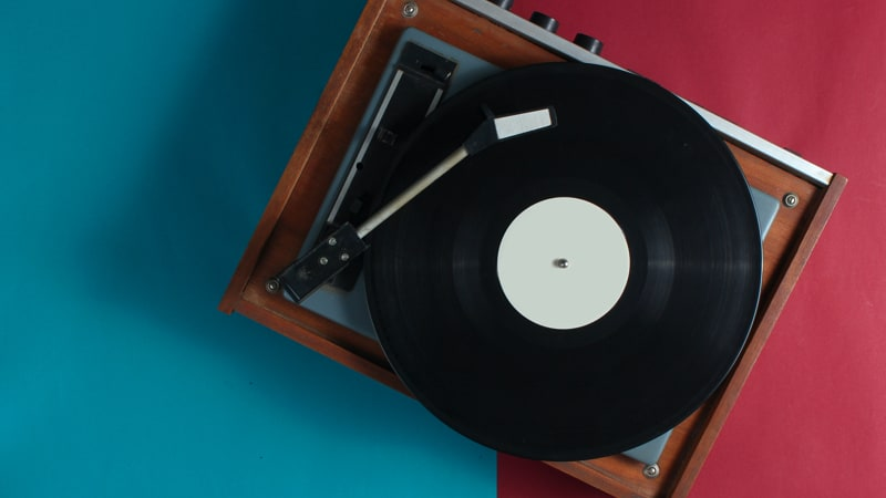Retro vinyl record player on red-blue background. Top view Image