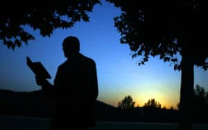 David L. Robbins reading a book at twilight Image