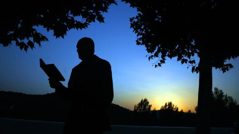 David L. Robbins reading a book at twilight Image