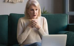 Senior woman shocked at what she sees on her laptop Image