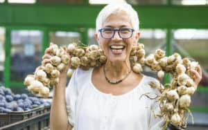 Senior woman keeping the flu and vampires away with superfoods like garlic Image