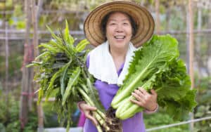 An Asian woman who is a farmer that just loves greens and vegetables Image