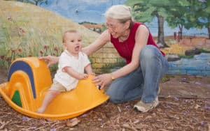 Grandma playing with her grandson in a toy rocking thing Image