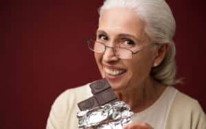Senior woman loving herself some dark chocolate Image