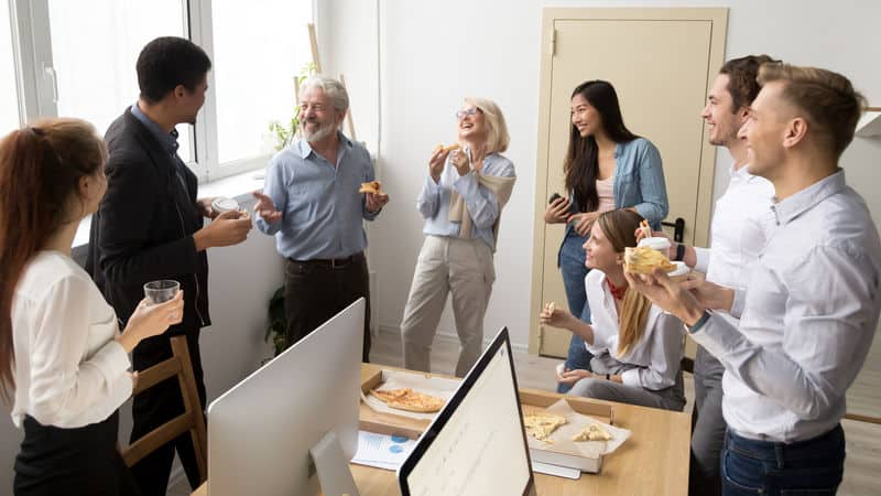 Coworkers eating lunch at work and laughing about it Image