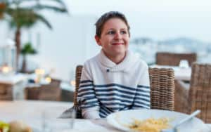 Teenager at the table with bad table manners Image