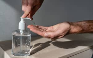 COVID-19: Man using hand sanitizer because he's so worried about it Image