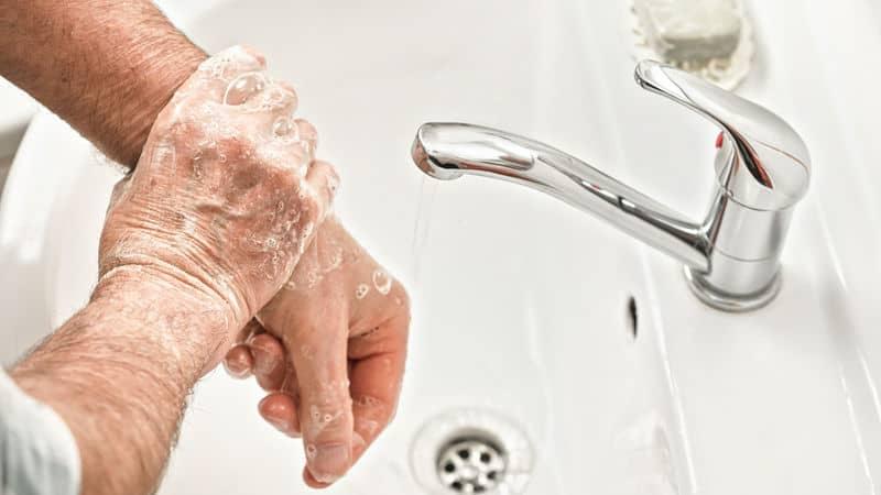 Senior practices good hygiene with handwashing Image