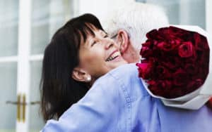 Woman hugging man holding roses while having boy problems Image