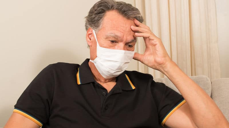 Man taking COVID-19 precautions with a face mask Image