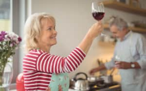 Man cooks dinner while alcoholic wife stares lovingly at her glass of wine Image