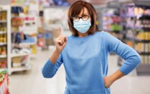 Woman practicing COVID-19 courtesy by wearing a mask to the grocery store Image