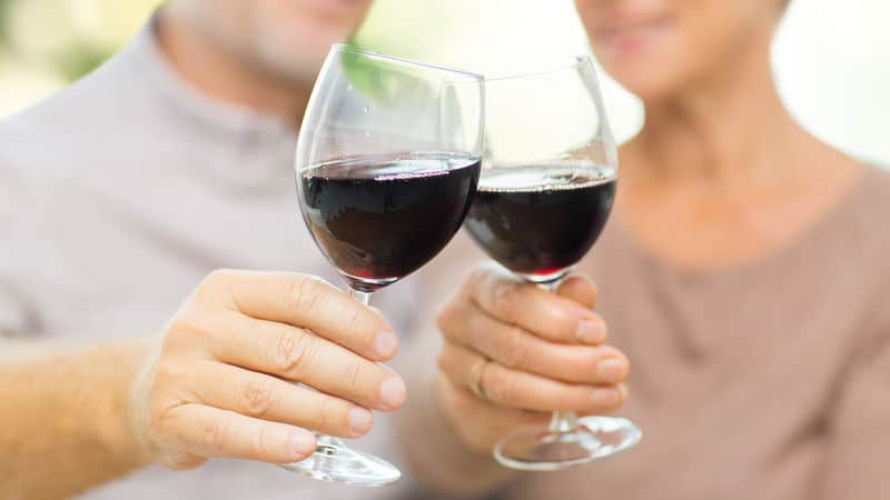 Two seniors drinking red wine because they are healthy Image