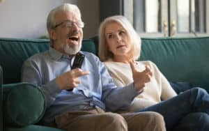 Angry father-in-law watching TV with his wife who looks like she regrets marrying him in the first place Image