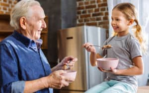 Grandfather eating healthy cereal with his granddaughter Image