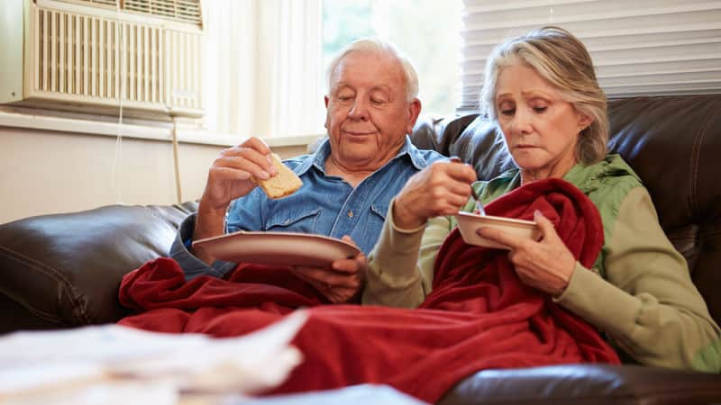 Senior couple stress eating on the couch Image