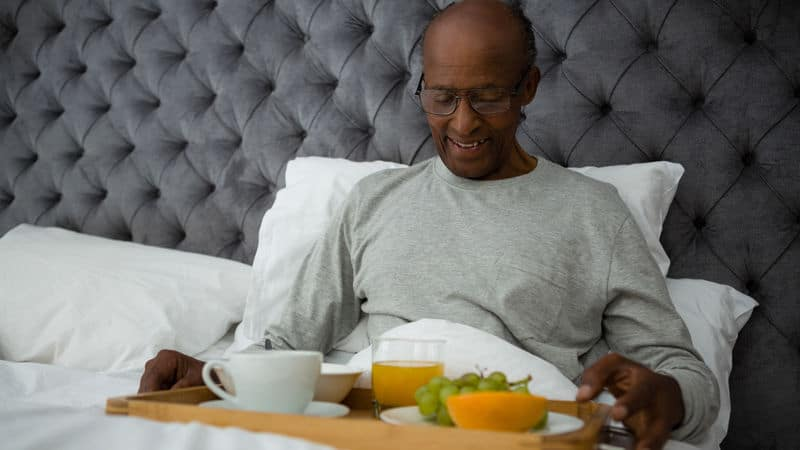 Senior man eating breakfast in bed Image