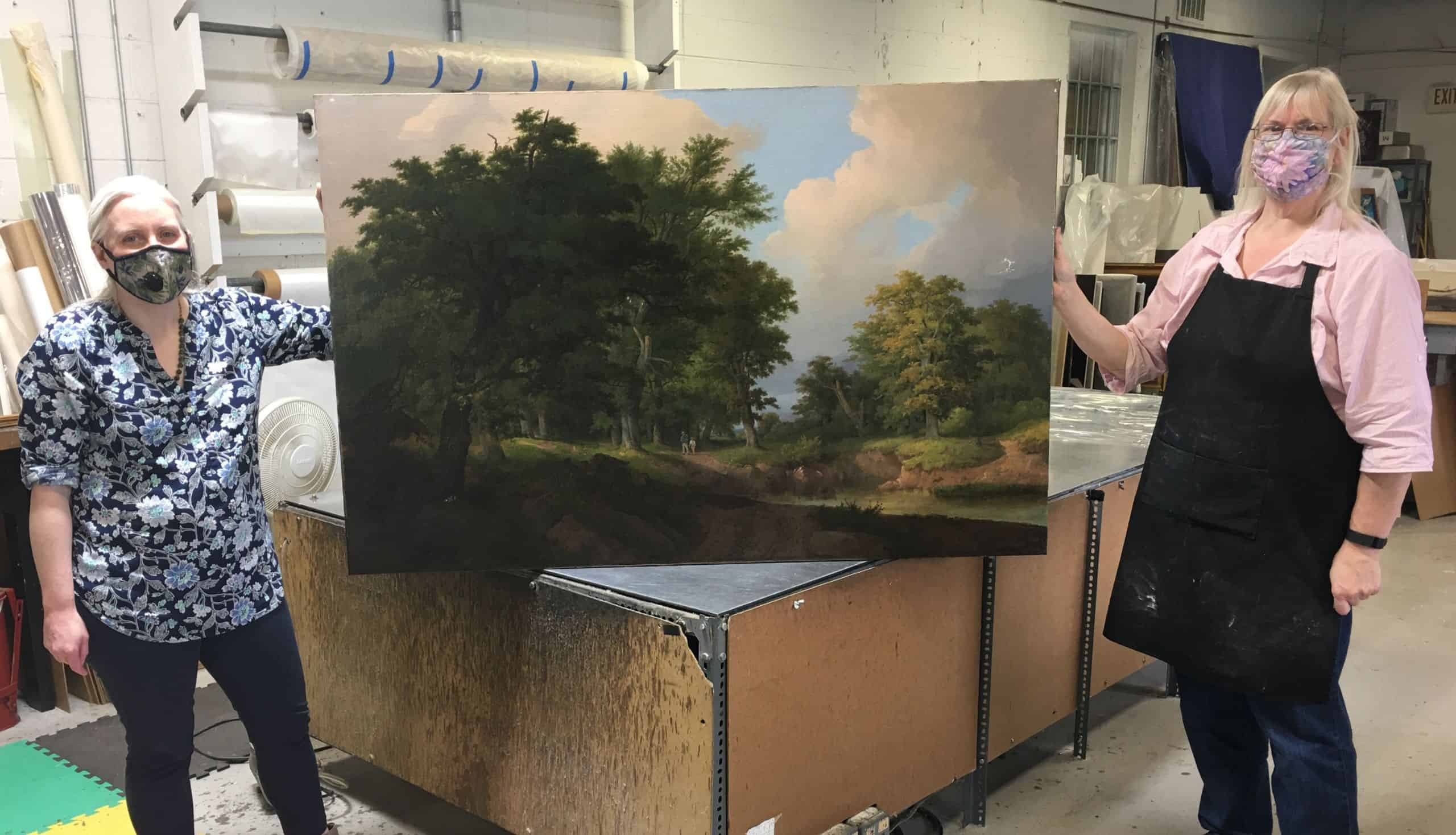 Art conservators Lorraine Brevig and Beth Fulton with an early American landscape in the process of being conserved