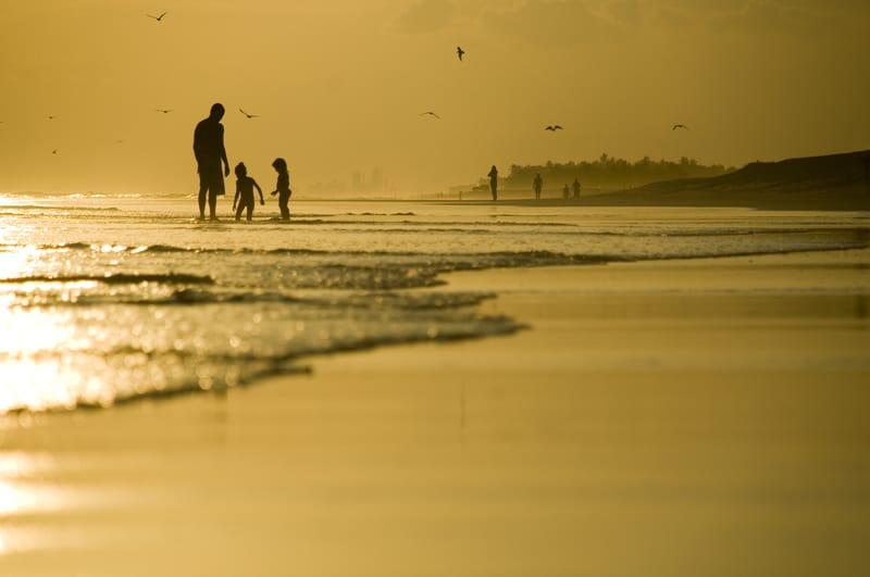 Dad with kids at seashore is part of childhood beach memories