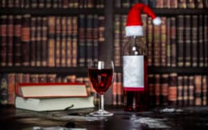 Books in a library, wine, and Christmas hat Image