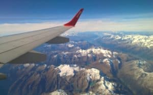 travel insurance benefits and warnings - view of mountain range from airplane Image