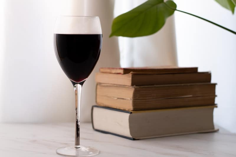 A glass of red wine and classic books
