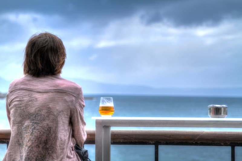 Woman gazing at gray sky and ocean while enjoying a beer