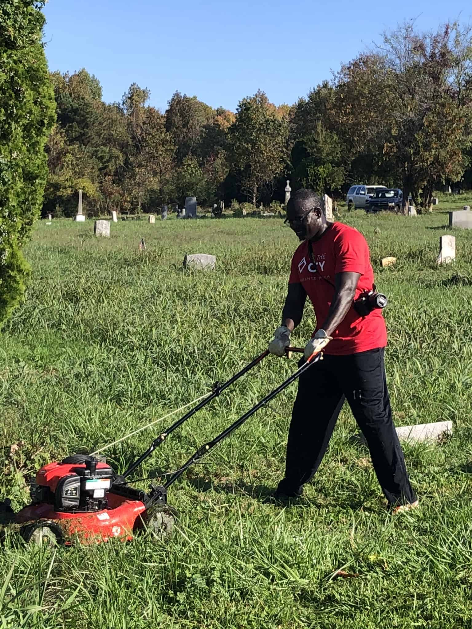 Volunteer mowing at Woodland Cemetery, a historic African American cemetery in Richmond, Virginia
