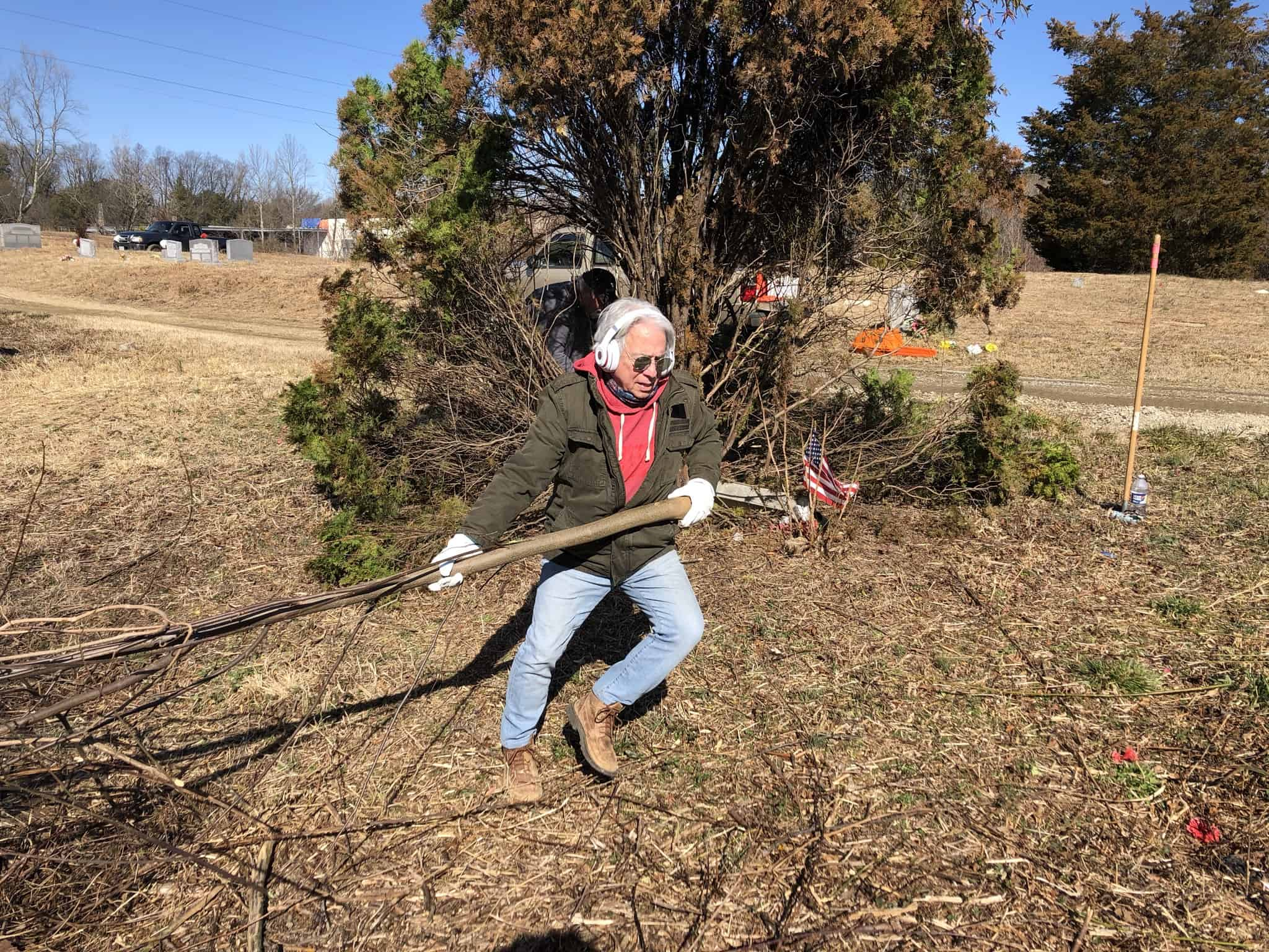 Volunteer clearing brush at Woodland Cemetery, a historic African American cemetery in Richmond, Virginia