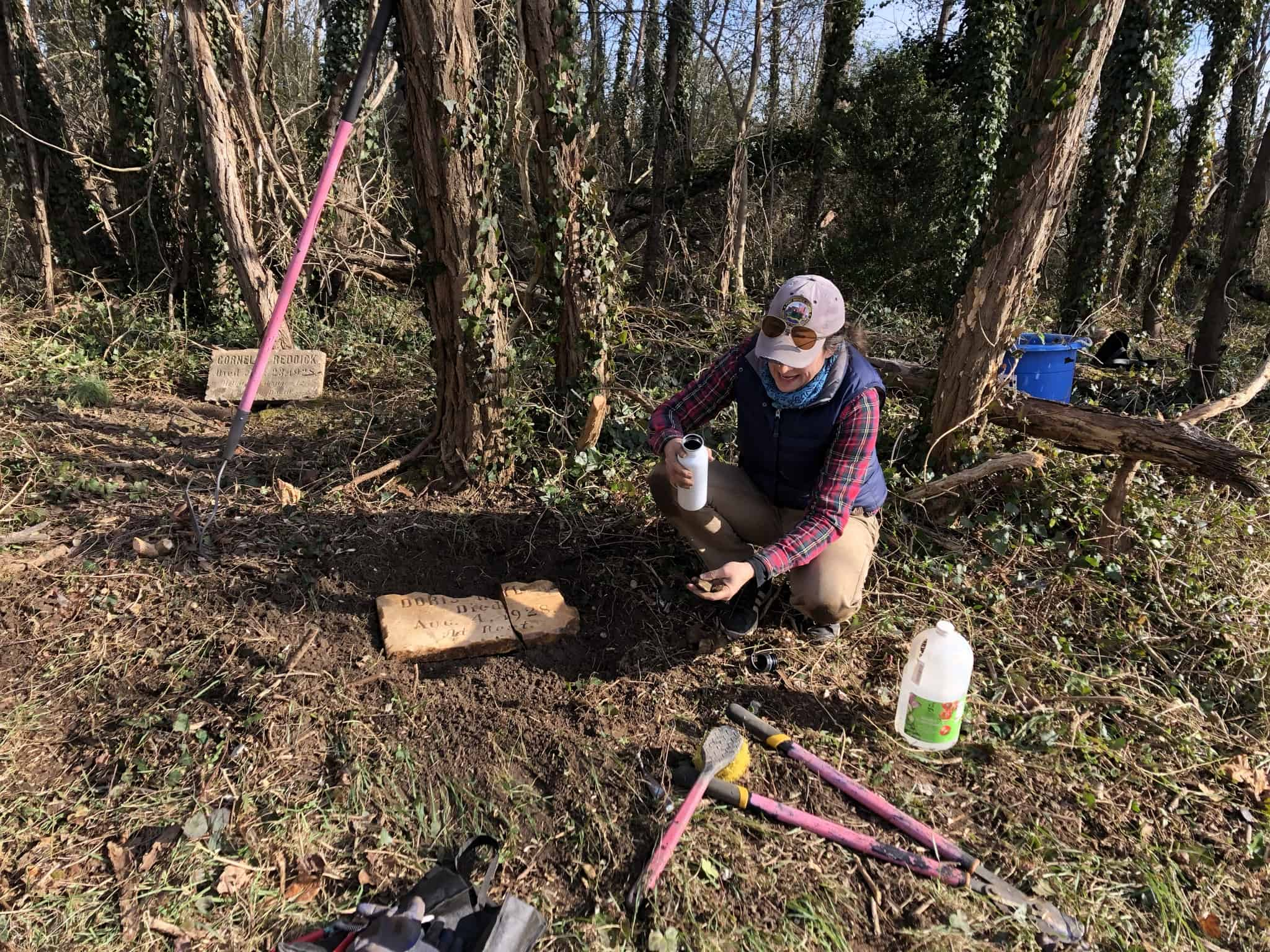 Volunteer tending a gravesite at Woodland Cemetery, a historic African American cemetery in Richmond, Virginia