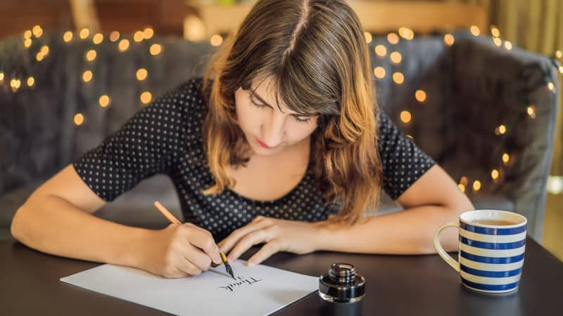 Millennial writing a thank you note Image