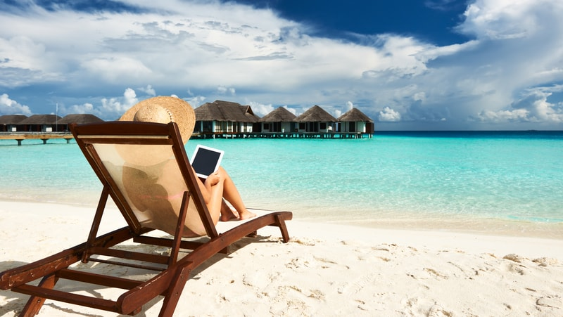 Woman on a tropical beach reading on a tablet. For Boomer expands in the digital world Image