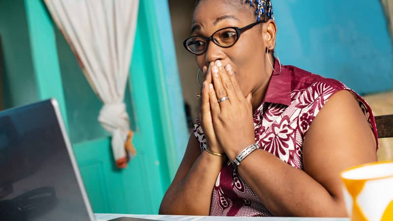 Shocked woman in front of her laptop looking at Facebook posts Image